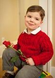 El muchacho joven que llevaba a cabo rojo se levantó Fotos de archivo libres de regalías