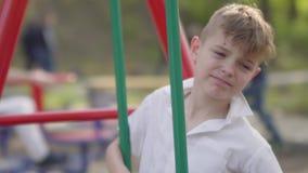 El muchacho joven que lloraba cerca del oscilación, niño se dañó Reconstrucci?n al aire libre almacen de video