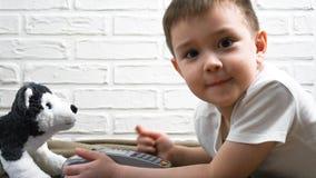 El muchacho joven que miente en el piso que presiona el terminal de la posición abotona Tecnologías modernas para los niños Práct Fotografía de archivo libre de regalías