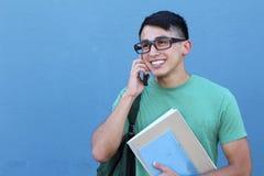 El muchacho joven que se ríe planea en el teléfono con el espacio para la copia Foto de archivo libre de regalías