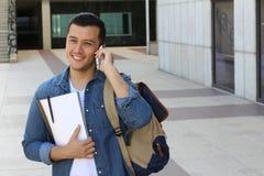 El muchacho joven que se ríe planea en el teléfono con el espacio para la copia Foto de archivo