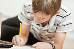 El muchacho joven que trabaja en una escuela proyecta en casa Fotos de archivo libres de regalías