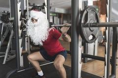 El muchacho joven realiza posiciones en cuclillas en las piernas que entrena con el coste de Santa Claus Fotos de archivo