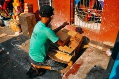 El muchacho joven recicla las cajas en Rangún Imagen de archivo