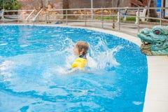 El muchacho joven salta en el agua de la piscina foto de archivo