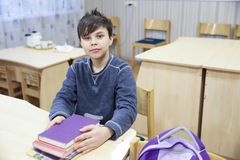 El muchacho joven se está sentando en la tabla con los libros en sala de clase Fotos de archivo