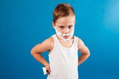 El muchacho joven serio en afeitar espuma le gusta el hombre que sostiene la maquinilla de afeitar Fotos de archivo libres de regalías