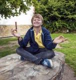 El muchacho joven sonríe y se divierte meditando Foto de archivo libre de regalías