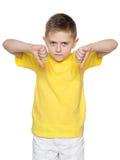El muchacho joven sujeta sus pulgares hacia abajo Fotografía de archivo