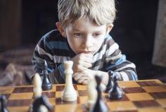 El muchacho juega a ajedrez Foto de archivo