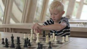 El muchacho juega a ajedrez El ni?o hace el movimiento a un oficial metrajes