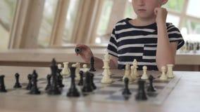 El muchacho juega a ajedrez El ni?o se sienta en un club de ajedrez brillante espacioso almacen de metraje de vídeo