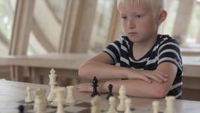 El muchacho juega a ajedrez El ni?o se sienta en una tabla con las figuras almacen de metraje de vídeo