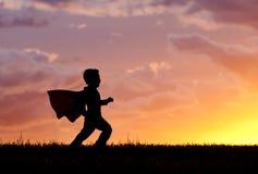 El muchacho juega al héroe estupendo en la puesta del sol. Imagenes de archivo