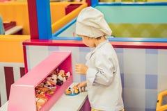 El muchacho juega al juego como si él fuera cocinero o panadero en una cocina del ` s de los niños imagenes de archivo