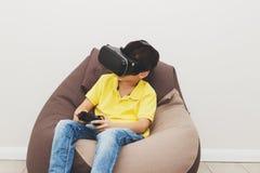 El muchacho juega al juego con los vidrios de la realidad virtual dentro Imagen de archivo