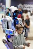 El muchacho juega con gestos con un robot blanco como muestra del frie Imagenes de archivo