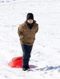 El muchacho juega con la sacudida en la nieve en las montañas Fotos de archivo