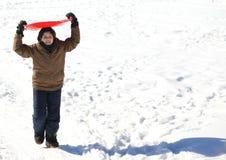 El muchacho juega con sledging en invierno en la nieve blanca Imagen de archivo