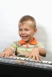 El muchacho juega el piano Imagen de archivo