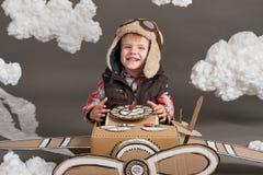 El muchacho juega en un aeroplano hecho de la caja de cartón y de sueños de hacer piloto, nubes de la algodón en un fondo gris fotos de archivo