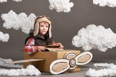 El muchacho juega en un aeroplano hecho de la caja de cartón y de sueños de hacer piloto, nubes de la algodón en un fondo gris imagen de archivo libre de regalías