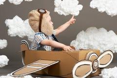 El muchacho juega en un aeroplano hecho de la caja de cartón y de sueños de hacer piloto, nubes de la algodón en un fondo gris, r imagen de archivo