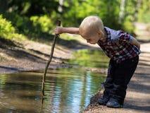 El muchacho juega en un pequeño río en un día de verano soleado Foto de archivo