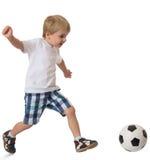 El muchacho juega a fútbol Foto de archivo