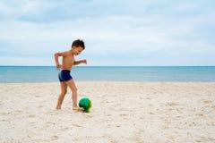 El muchacho juega a fútbol en la playa Imagenes de archivo