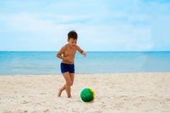 El muchacho juega a fútbol en la playa Fotografía de archivo