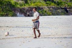 El muchacho juega a fútbol en una playa Imagen de archivo libre de regalías