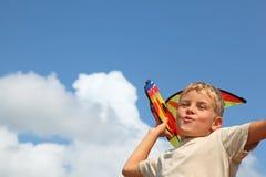 El muchacho juega la cometa contra el cielo Foto de archivo