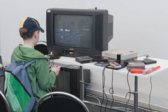El muchacho juega la consola del juego con la televisión en Animefest Imagen de archivo
