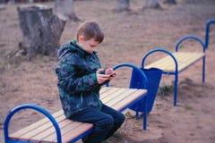 El muchacho juega a un juego en su teléfono móvil que se sienta en el parque en un banco Fotos de archivo
