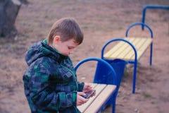 El muchacho juega a un juego en su teléfono móvil que se sienta en el parque en un banco Imágenes de archivo libres de regalías