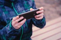 El muchacho juega a un juego en su teléfono móvil que se sienta en el parque en un banco Manos del ` s del muchacho del primer Imagen de archivo libre de regalías