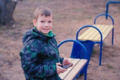 El muchacho juega a un juego en su teléfono móvil que se sienta en el parque en un banco Mirada de la cámara y sonrisa Fotografía de archivo libre de regalías