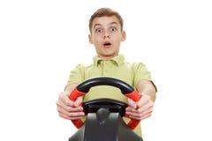 El muchacho juega una videoconsola de conducción, aislada en blanco Imagen de archivo