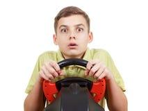 El muchacho juega una videoconsola de conducción, aislada en blanco Imagenes de archivo