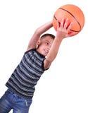 El muchacho, jugador de básquet hace un tiro con una bola Imagenes de archivo