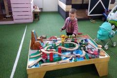 El muchacho a la edad de 3 años de juegos con el ferrocarril de los niños de madera en una esquina en centro de entretenimiento,  imagen de archivo