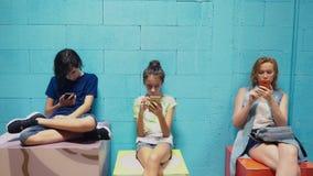 El muchacho, la muchacha y la mujer utilizan sus teléfonos móviles mientras que se sienta contra la pared azul almacen de video