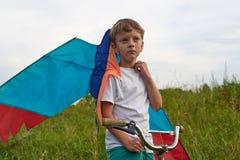 El muchacho lanza en el cielo azul una cometa imagenes de archivo