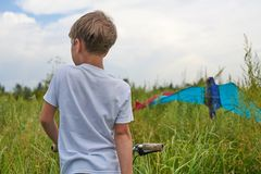 El muchacho lanza en el cielo azul una cometa imagen de archivo libre de regalías
