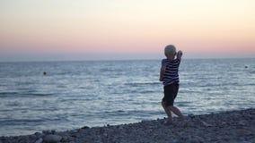 El muchacho lanza piedras en el mar en la puesta del sol metrajes