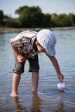 El muchacho lanza un pequeño barco de vela en el río Foto de archivo libre de regalías