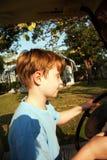 El muchacho le gusta conducir un coche eléctrico Fotos de archivo libres de regalías