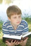 El muchacho lee el libro imagen de archivo