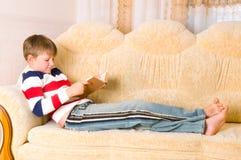 El muchacho lee el libro fotografía de archivo